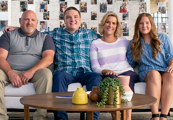 AdoptUSKids spokesfamily, the Thompsons sitting on a sofa